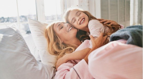 mom waking up hugging daughter