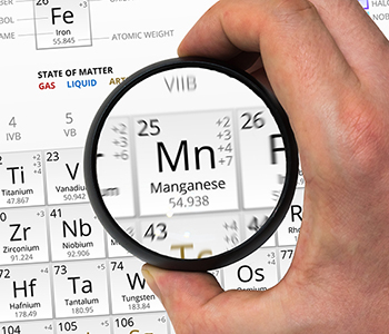 Manganese symbol - Mn. Element of the periodic table zoomed with magnifying glass
