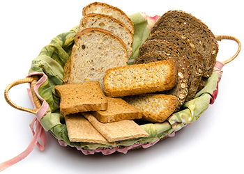 Different sorts of toasts in a basket, isolated on white