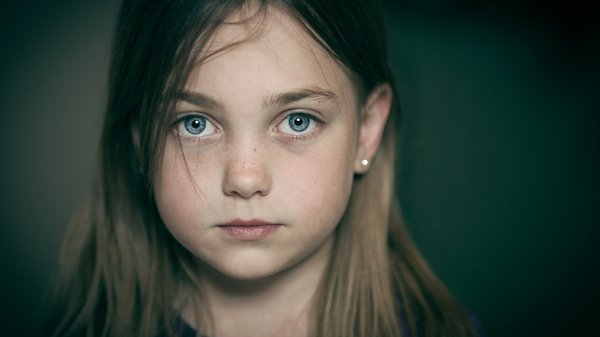 Portrait of bright eyed young girl in pensive and melancholy mood.