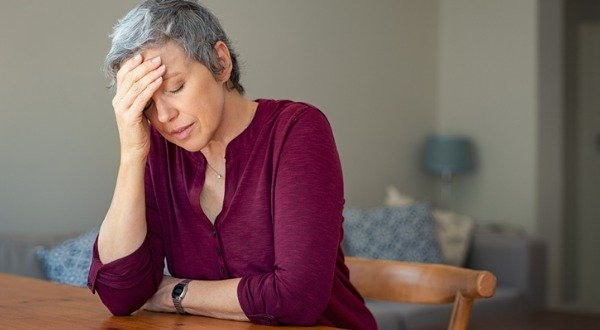 stressed senior woman at kitchen table