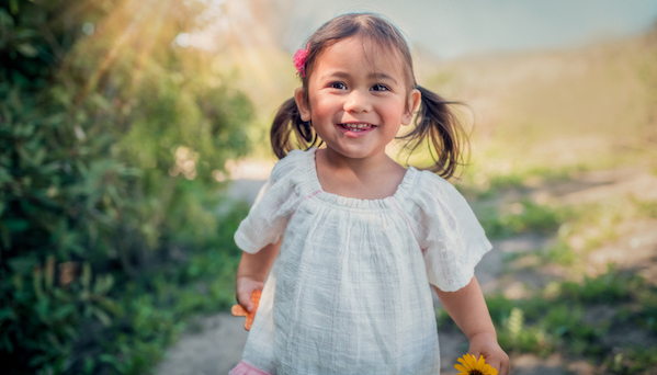 girl playing outdoors carrying sunflower